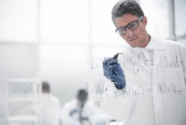 Serious scientist writes a formula on a glass Board .photo with copy space stock vector