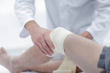Doctor treats wound on the patients leg in a clinic room