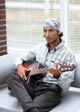 Handsome businessman playing the guitar in office
