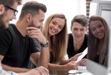 Group of three people analyze data on desktop computer.