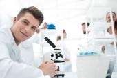 Veselá laboratorní pracovník pomocí mikroskopu v laboratoři
