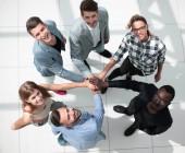 Ansicht von oben. multinationale Kollegen stehen im Büro und halten