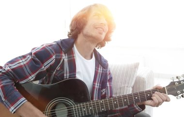 modern guy playing guitar sitting on the couch. concept of a lifestyle