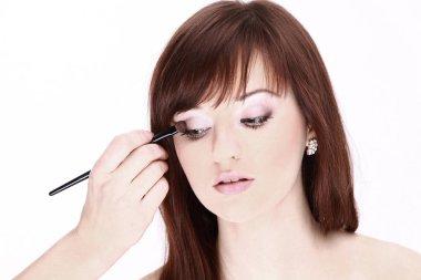 closeup.Makeup artist applies eye shadow. Beautiful woman face