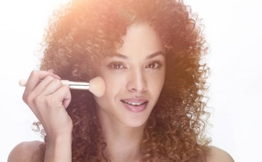 beautiful young woman with a make-up brush.