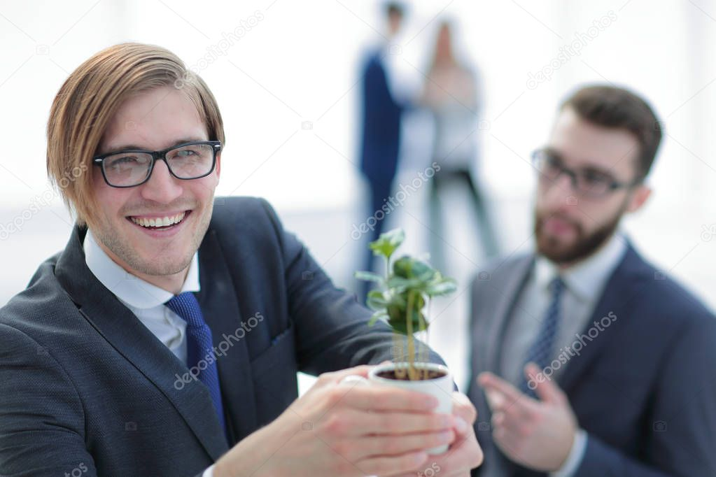 young businessman shows you a young sprout