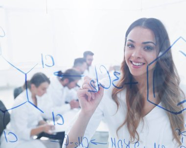 smiling female assistant makes an entry on the Board.