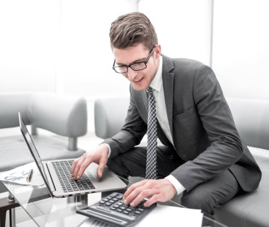 young businessman using calculator and laptop