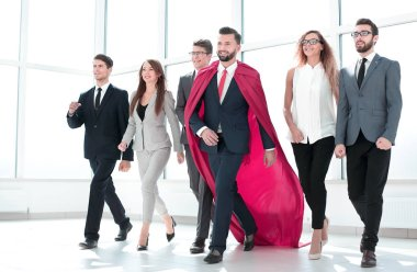 businessman in a red cloak marching with the business team