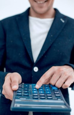 close up.smiling businessman counting profits on calculator.