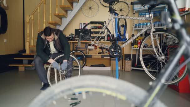 Der gut aussehende Mechaniker befestigt das Hinterrad mit einem Schraubenschlüssel, während er am modernen Arbeitsplatz auf einem Holzhocker sitzt. Zyklen, Ersatzteile, Werkzeuge und Geräte sind sichtbar.
