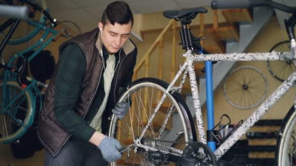 Tapasztalt szerelő van szerelés kerékpár hátsó kerék beállító munkahelyi jármű karbantartás során. Szakmai eszközök, alkatrészek és berendezések témához.