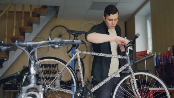 Zkušený mistr je kontrola a oprava jízdních kol řídítka se speciálními nástroji při práci v dílně s četnými náhradních dílů a zařízení.