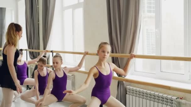 Diligent Young Ballet Dancers Are Doing Plie And Battement Tendu