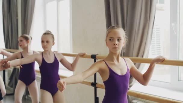 Niedliche kleine Mädchen haben Choreografieunterricht und machen Übungen an der Ballettbar, während ihr Lehrer ihnen hilft, Handpositionen zu korrigieren und mit ihnen zu sprechen..