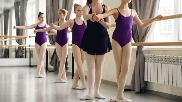 Ballet teacher is helping her small female students with arms, hands and legs positions during lesson in dancing school. Girls are wearing trendy ballet suits and pointe-shoes.