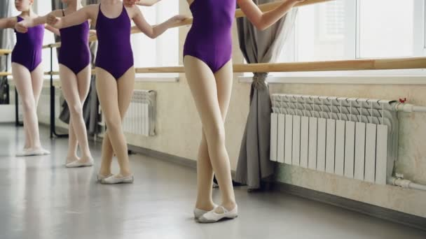 Little ballet-dancers are practising battement tendu during lesson in ballet school. Bright bodysuits, white pointe-shoes, ballet barre and light dancing hall are visible.