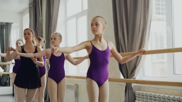 Serious girls are practising arm movements during ballet lesson in studio. Teacher professional ballerina is helping them correcting positions and giving instructions.