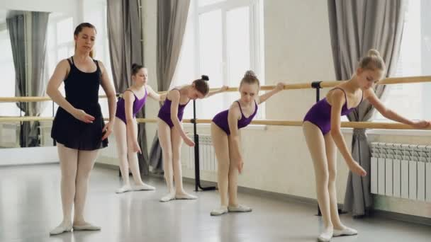 Diligent girls are learning forward and backward bends and arm movements during ballet lesson with strict teacher. Students wearing beautiful bodysuits are holding ballet barre.
