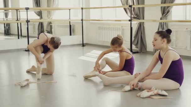 Adorable young ballet dancers are putting on ballet slippers and talking sitting on floor of light studio. Footwear, children and communication concept.