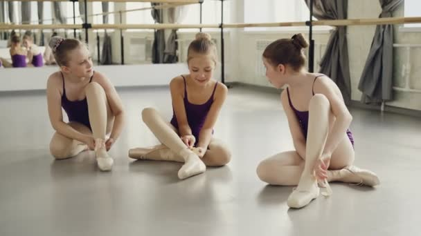 Three cute girls are trying to put on ballet slippers sitting on studio floor together and chatting emotionally getting ready for choreography class.