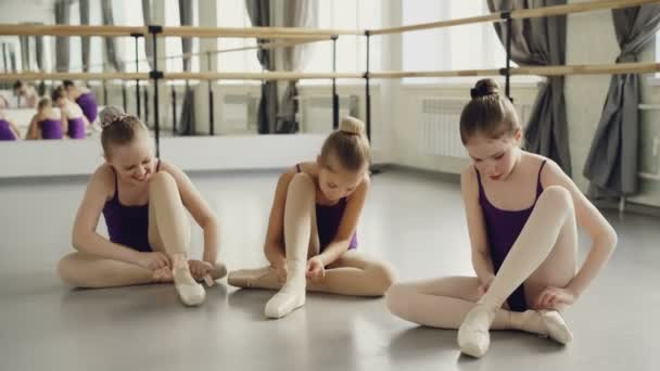 Slim pretty children are wearing ballet slippers on studio floor and talking. Large mirror, ballet barre, bright bodysuits and beautiful interior are visible.