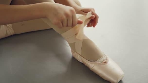 2b54490f9 Toma primeros planos de pies de chicas en zapatillas de ballet y las manos  tratando de poner en el calzado y atar la cinta alrededor de la pierna muy  bien. Zapatos de Pointe, baile y vestimenta ...