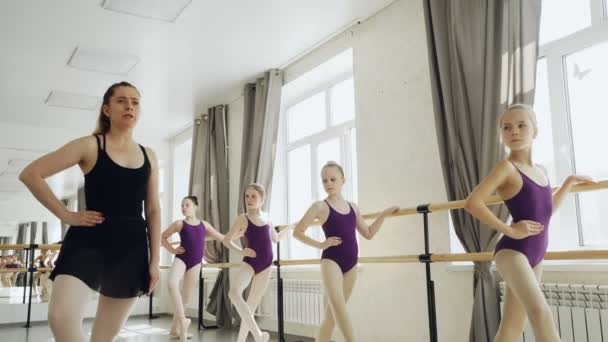 Strict ballet teacher is demonstrating legs and arms positions while diligent little girls are repeating after her holding ballet bar and looking at tutor.