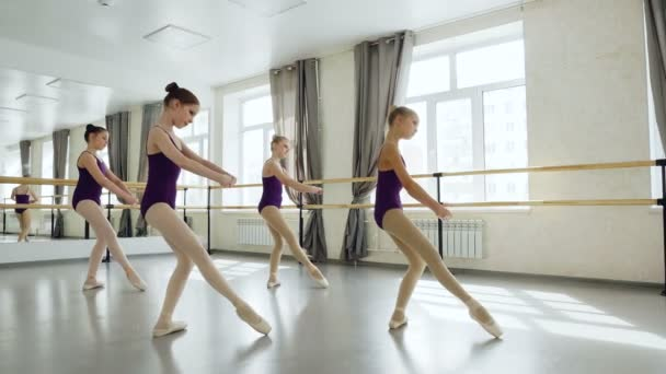 Anmutige kleine Balletttänzerinnen in wunderschönen Trikots üben im leichten Studio Bewegungen ein. Hübsche Mädchen ziehen gleichzeitig zusammen.