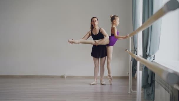 Fleißige kleine Ballettschülerin im Body hat individuellen Ballettunterricht mit professionellem Lehrer, der Bewegungen lernt und das Bein nach hinten hebt.