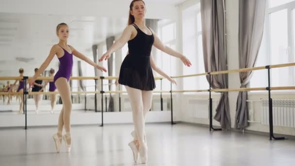 Two girls ballet dancers are practising dancing on tiptoes with their experienced teacher during ballet lesson in studio. Large mirror, ballet barre and windows are visible.