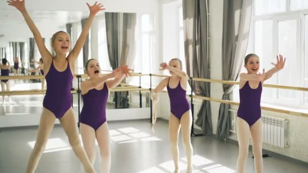 Slow motion of young girls starting ballet dancers jumping and shouting happily in light studio with ballet barre and mirror. Childhood and happiness concept.