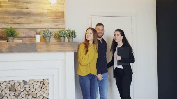Veselý realitní setkání krásný mladý pár v novém domě, otevření dveří, ukazující dokumenty a mluvit s klienty. Šťastní lidé a konceptem prodeje nemovitostí