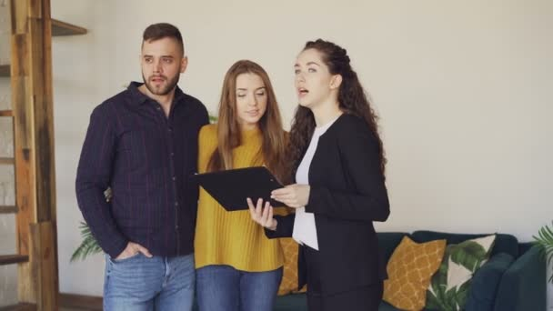 Vidám ház ügynöke beszél vevők imádnivaló fiatal pár megvitatni az értékesítés feltételei, és bemutatja a papírokat. Ügyfelek izgatottak az új lakás