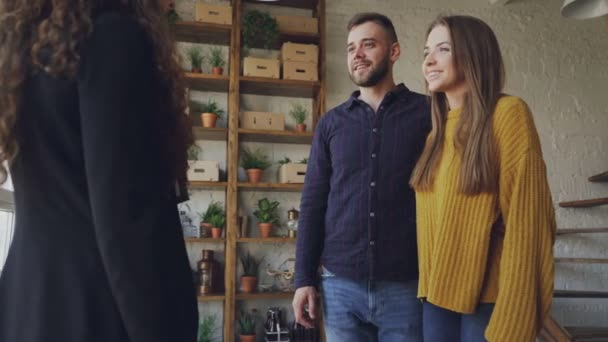 Happy young couple is buying new house shaking hands with female realtor then hugging and laughing. Relocation, happiness and accommodation concept.