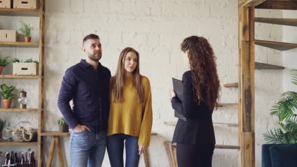 Attraktives Paar berät Immobilien-Deal mit weiblichen Grundstücksmakler innen schönes Haus stehen, schaut sich um und sprechen. Unterkunft und Menschen-Konzept