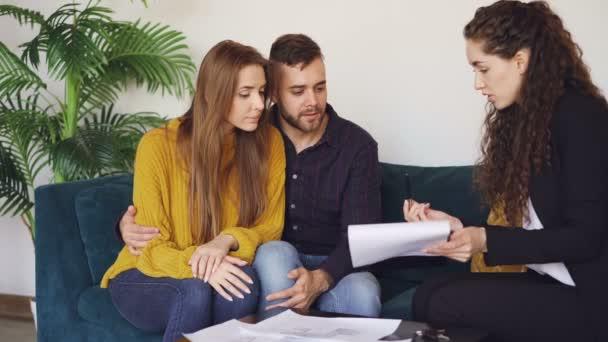 Podnikatelka je prodej domu, aby manželský pár, šťastný, že manžel je podepisování koupit a prodat dohody, třes rukou realitní kanceláře a přijímání klíč pak líbat jeho žena