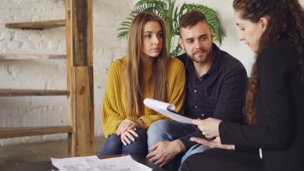 Dům kupující pohledný muž je podepisování prodejní smlouvu s agentem bydlení, získali klíč a líbá svou přítelkyni po vyjednávání s nemovitostmi. Nákup nemovitostí koncept