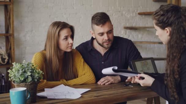 Atraktivní broker je prodej domu na mladý pár, lidé jsou podepisování dokumentů a potřesení rukou, realitní dává klíč k novému majiteli, on líbá svou ženu