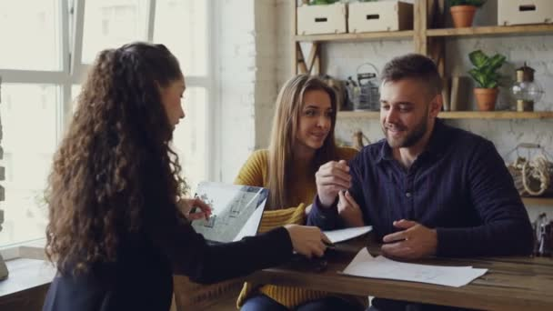 Mladí manželé kupují byt podepisování dokumentů a líbat, zatímco realitní kanceláře je dávat klíče k novým majitelům po úspěšné řešení pak práci s notebookem