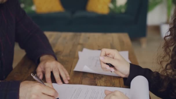 Close-up shot of male hand signing purchase and sell agreement and taking house keys from realtor then shaking hands. Selling and buying real estate concept.