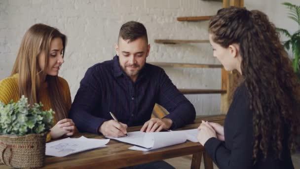 Milující pár se nákup domu podepisování prodejní smlouvu s agentem bydlení, obstarat klíč a objímání po provedení se zabývají realitní. Nákup nemovitostí koncept