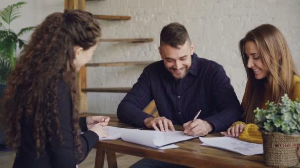 Mladí lidé se smějí a podepisování nakupovat a prodávat smlouvy pak brát klíčové a objímání při setkání s nemovitostmi. Nákup a prodej vlastnost konceptu