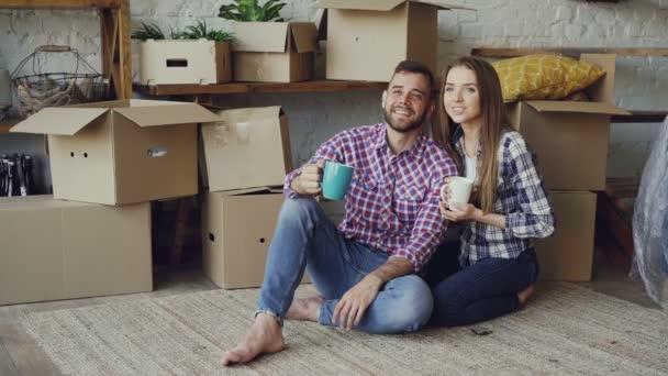 Přítelkyně a přítel mluví dělá plány sedí na podlaze nové kupovaným bytem, rozhlížel se kolem a držení hrnky. Vztah a přemístění koncept.