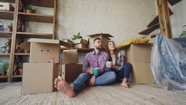 Roztomilý pár se mluví, líbání a držení hrnky zatímco sedí na podlaze nového bytu po přemístění. Mnoho polí, balení nábytku a rostliny jsou viditelné.