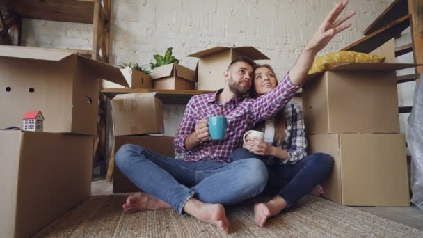 Young husband and wife are talking, looking around and kissing sitting on floor after moving to new house. Nice interior and many boxes with personal things are visible.