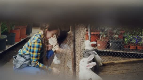 Mother and little daughter farmers are feeding rabbit in cage, watching them eat and laughing. Domestic animals, happy childhood and farming concept.