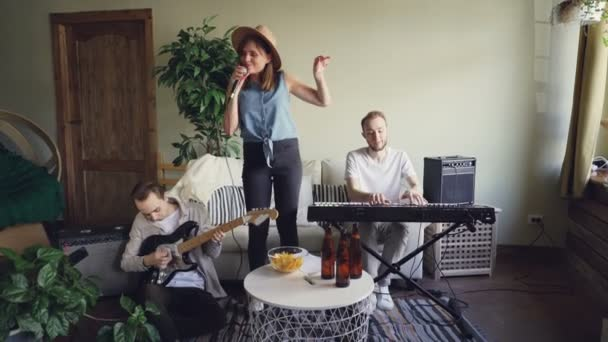 Emotional female singer is singing and dancing while guitarist and vocalist are playing musical instruments. Happy young people and music concept.