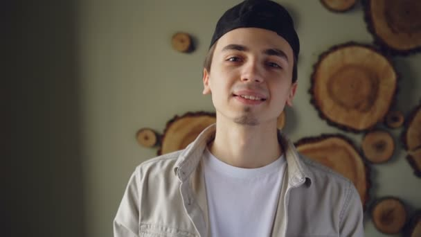 Close-up portrait of handsome young man wearing black cap, white T-shirt and beige shirt looking at camera and smiling. Attractive people and fashion concept.
