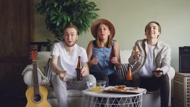 Nervös Fans attraktive junge Leute sind gerade Spiel am Tv und jubeln über Bier und Snacks dann feiern Erfolg mit hohen fünf und aufgeregt Gesten.
